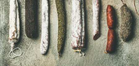 Variety of Spanish or Italian cured meat sausages. Flat-lay of fuets and salamies over rough grey concrete background, top view, copy space, wide composition