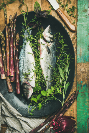 Cooking fish dinner. Flat-lay of raw incooked sea bass with herbs and vegetables over rustic wooden background, top view. Helathy, clean eating, dieting food concept Stock fotó - 102634046