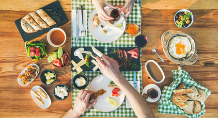 Couple having Turkish breakfast. Flat-lay of peoples hands and traditonal Turkish cuisine food for breakfast. Bread, ftied eggs, olives, vegetables, sausage, cheese and tea over wooden table, top view