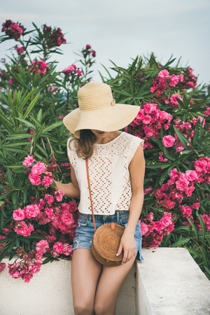 Young blonde slim girl in sunhat, lace top and denim shorts with straw round bag sitting on white parapet near blooming pink flowers of oleander tree at seaside. Summer travel lifestyle concept Stock Photo