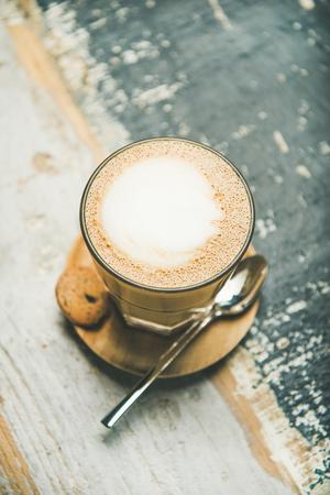 Latte coffee in glass over wooden textured background. Foto de archivo - 102634053