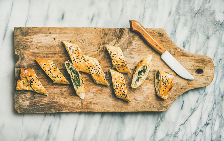 Flat-lay of freshly baked Turkish borek roll slices with spinach, feta cheese and black cumin seeds on wooden board over grey marble background, top view. Traditional East Mediterranean cuisine
