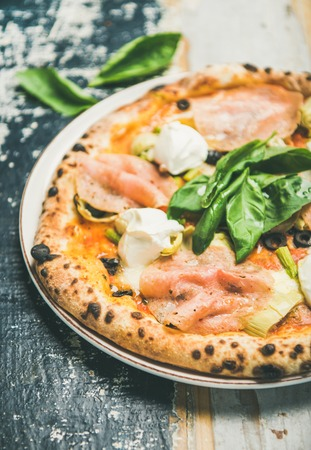 Italian lunch or dinner. Freshly baked pizza with artichokes, smoked turkey ham, olives, cream cheese and basil leaves over rustic wooden background, selective focus, close-up