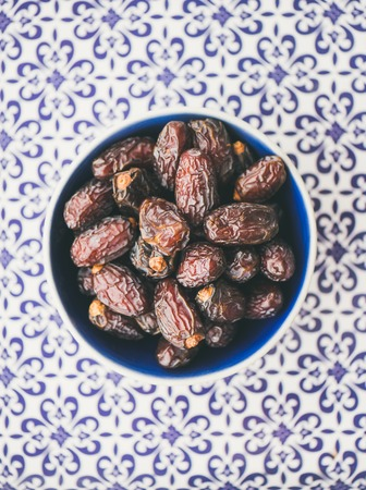 Traditional muslim food for Ramadan iftar meal. Dates over typical oriental ornamental painted background, top view