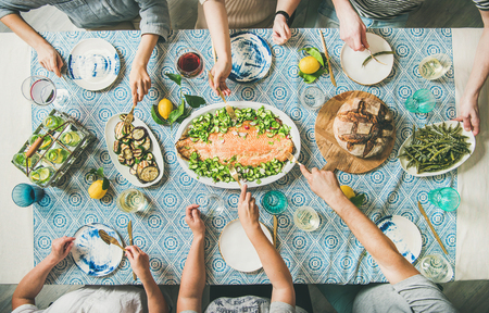Family or friends summer party or seafood dinner. Flat-lay of group of mutinational people with different skin color at big table eating delicious food together. Summer gathering or celebration Stock Photo - 103448631