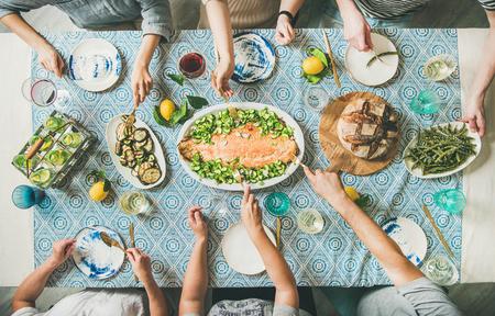 Sommerparty mit Familie oder Freunden oder Abendessen mit Meeresfrüchten. Flache Lage einer Gruppe von Meutern mit unterschiedlicher Hautfarbe am großen Tisch, die zusammen leckeres Essen essen. Sommertreffen oder Feiern Standard-Bild