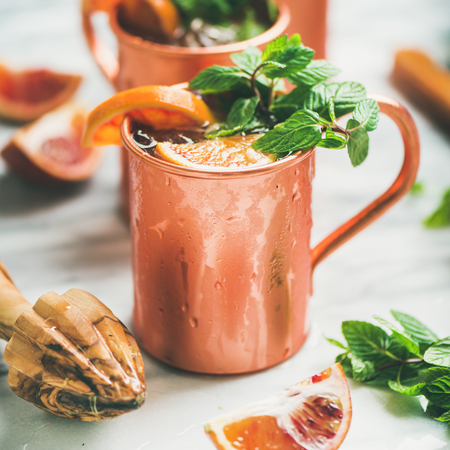 Blood orange Moscow mule alcohol cocktails with fresh mint and ice in copper mugs over white marble background, square crop Stok Fotoğraf