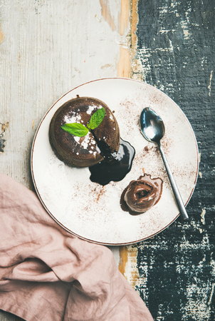 Flat-lay of hot chocolate souffle dessert cake with liquid filling and chocolate ice cream over rustic wooden background, top view, copy space Фото со стока - 104143853