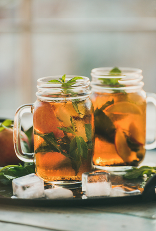 Summer refreshing cold peach ice tea with fresh mint leaves in glass jars on metal tray, selective focus, copy space, vertical composition