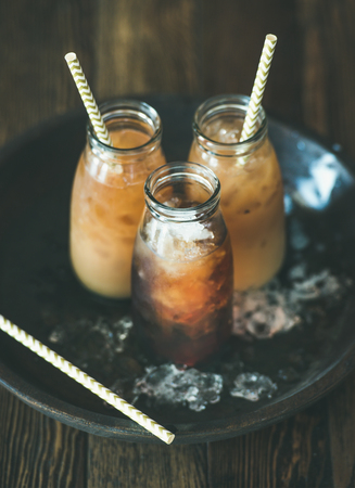 Refreshing summer drink. Cold Thai iced tea in bottles with milk on plate over dark wooden background, selective focus. Vegetarian, healthy food concept Stock Photo