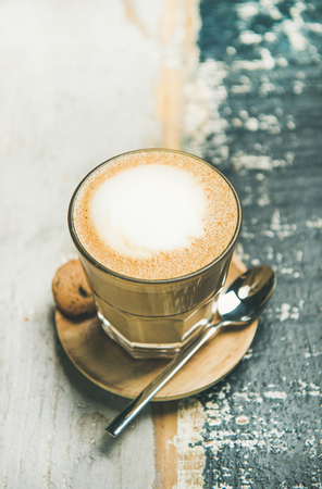 Classic foamy cappuccino coffee in glass over rustic wooden table background