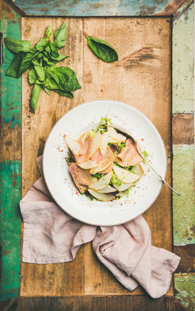 Flat-lay of fresh summer salad with smoked turkey ham and pear in white plate over rustic wooden background, top view