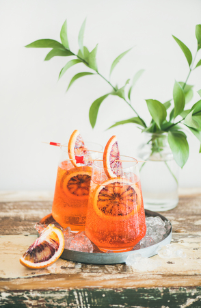 Two glasses of Italian Aperol spritz alcohol cocktail with ice and blood orange slices. Summer refreshing cocktail drink