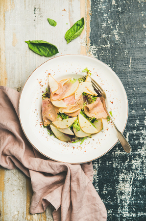 Flat-lay of fresh summer salad with smoked turkey ham and slices of pear in white plate over scorched rustic wooden table background, top view