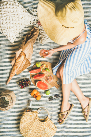Summer picnic setting. Woman in linen striped dress and straw sunhat with glass of rose wine in hand, fresh fruit and baguette on blanket, top view. Outdoor gathering or lunch Stock Photo