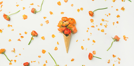 Flat-lay of waffle sweet cone with orange buttercup flowers over white background, top view. Spring or summer mood concept