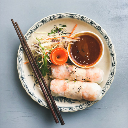 Asian style dinner. Flat-lay of summer rice paper rolls with shrimp and teriyaki sauce in bowl over blue table, top view, copy space, square crop. Chinese cuisine