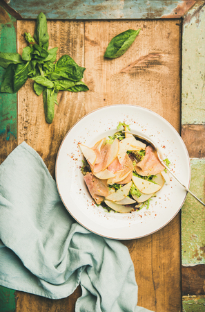Flat-lay of fresh summer salad with smoked turkey ham and pear in white plate over rustic wooden table background, top view