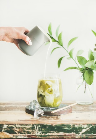Iced matcha latte drink in tumbler glass with coconut milk pouring from pitcher by hand, white wall and green plant branches at background, copy space. Summer refreshing vegan beverage cold drink Reklamní fotografie