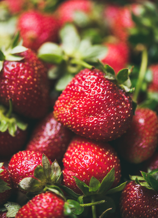 Fresh strawberry texture, wallpaper and background. Wet strawberries with leaves, selective focus. Summer food or local market produce concept