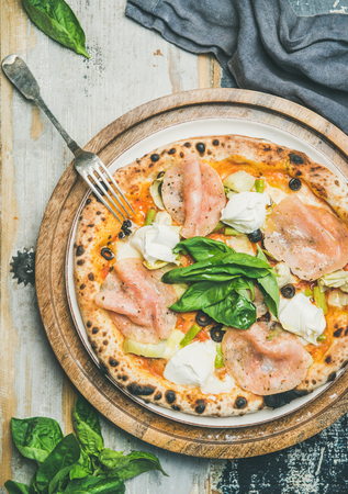 Italian lunch or dinner. Flat-lay of freshly baked pizza with artichokes, smoked turkey ham, olives, cream cheese, green basil leaves on tray over rustic wooden background, top view Stock Photo