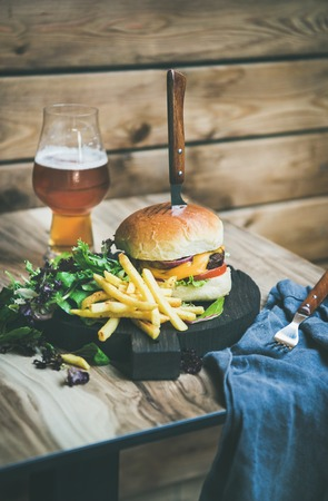 Classic burger dinner. Beef meat homemade burger with glass of lager beer, French fries and salad on dark wooden serving board, rustic wooden wall at background, copy space, vertical composition Stock Photo