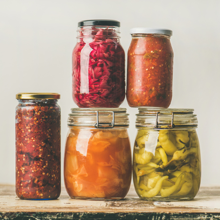 Autumn seasonal pickled or fermented colorful vegetables in glass jars placed in stack over vintage kitchen drawer, white wall background, square crop. Fall home food preserving or canning