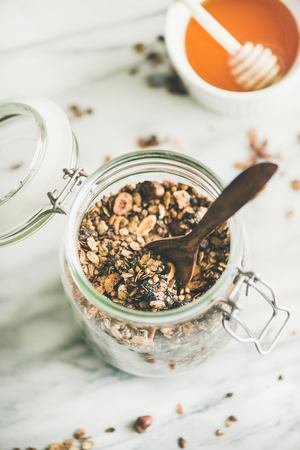 Healthy breakfast preparation. Buckwheat and chocolate granola with hazelnuts in glass jar over light marble background, top view. Clean eating, vegan, vegetarian food concept Stock Photo