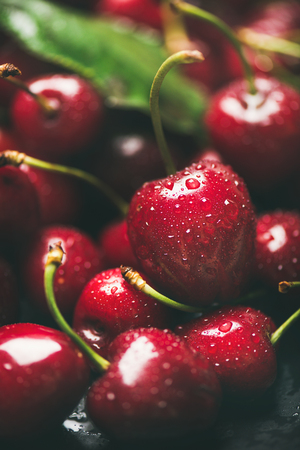 Fresh sweet cherry texture, wallpaper and background. Wet sweet cherries with leaves on dark background, selective focus, close-up, vertical composition. Summer food or local market produce concept Stok Fotoğraf - 105625948