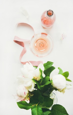Flat-lay of rose wine in glass and bottle, pink decorative ribbon, peony flowers over white background, top view, vertical composition. Summer celebration, wedding greeting card, invitation concept