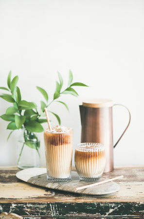 Iced coffee in glasses with milk and straws on board over rustic wooden table, white wall, jug and plant branch in vase at background, copy space. Summer refreshing beverage, ice coffee drink concept