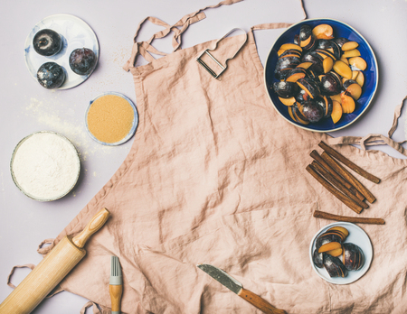 Baking ingredients and tools. Flat-lay of dusty pink linen apron, kitchen utensils, flour, sugar, fruit and spices over pastel lilac background, top view, copy space