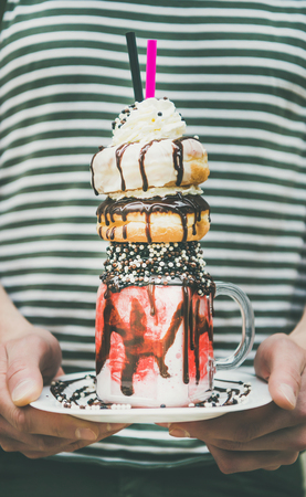 Man in striped clothing holding summer cold strawberry donut freakshake drink with whipped cream in mason jar in hands, selective focus, vertical composition