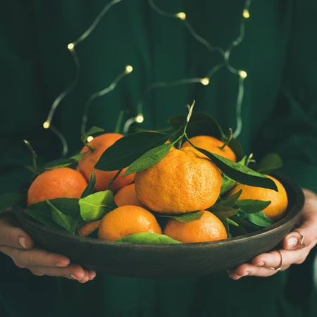 Fresh raw tangerines citrus fruits in plate in hands of girl wearing green dress with holiday lights bokeh, selective focus, copy space, square crop. Winter Christmas of New year holiday mood