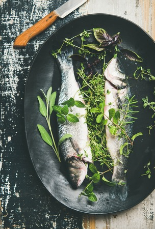 Cooking fish dinner. Flat-lay of raw uncooked sea bass fish with green herbs on black plate over rustic wooden painted background, top view, square crop. Helathy, clean eating, dieting food concept Banco de Imagens