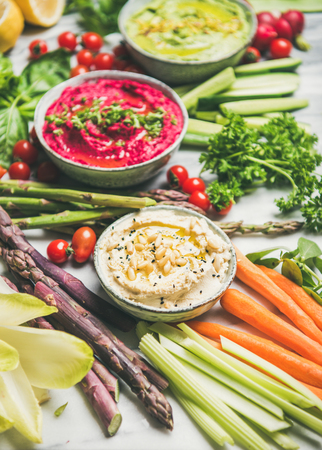 Healthy raw summer vegan snack plate. Chickpea, beetroot, spinach hummus dips with colorful fresh vegetables and greens on white table background. Clean eating, dieting, vegan or vegetarian party food