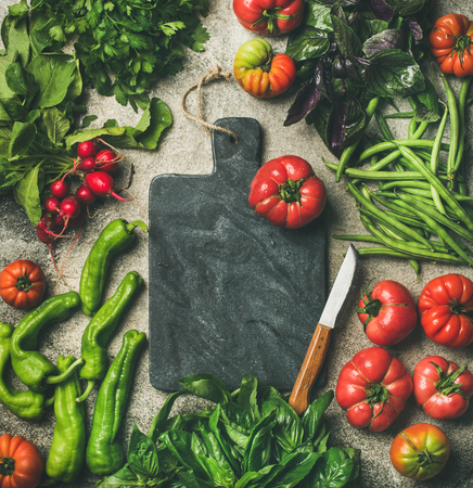 Healthy seasonal food cooking background. Flat-lay of vegetables and greens over concrete background, black marble chopping board in center, top view, copy space. Clean eating, vegan food preparation