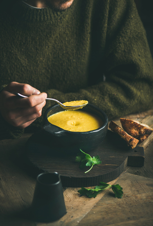 Man in dark winter sweater eating sweet corn and shrimp chowder soup from bowl. Autumn or winter warming food Stock Photo