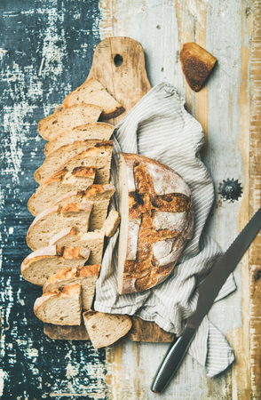 Flat-lay of freshly baked sourdough wheat bread loaf halved and cut in slices on board over linen napkin and rustic wooden table background, top view Stock Photo