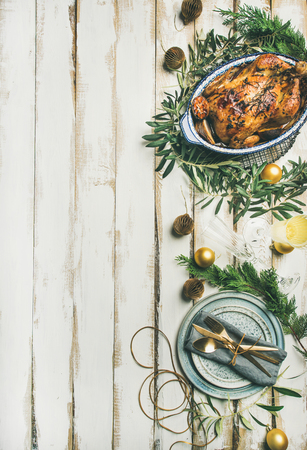 Christmas or New Year celebration table setting. Flat-lay of roast chicken, plates, silverware and toy holiday decoration over white wooden background, top view, copy space, vertical composition