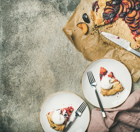 Flat-lay of plum galetta sweet cake in white plates over grey concrete background, top view, copy space. Seasonal Fall or Autumn dessert Stock Photo