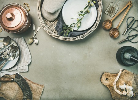 Food cooking minimalistic background. Flat-lay of various kitchen utensils, copper saucepan, vintage cutlery over grey concrete countertop background, top view, copy space