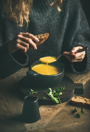 Woman in dark winter sweater eating sweet corn and shrimp chowder soup from black bowl with toasted bread, close-up. Autumn or winter warming food Stock Photo