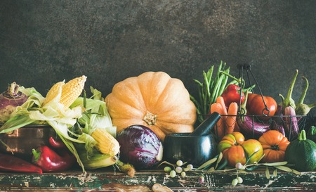 Fall vegetarian food ingredients. Assortment of various Autumn vegetables for healthy cooking over rustic cupboard, dark wall background, copy space. Local market organic produce
