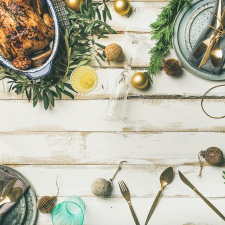 Christmas or New Year celebration table setting. Flat-lay of roast chicken, plates, silverware, glass and toy holiday decoration over rustic white wooden background, top view, copy space, square crop