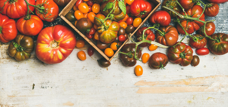 Flat-lay of fresh colorful ripe Fall or Summer heirloom, bunch and cherry tomatoes over rustic wooden background, top view, copy space. Local market seasonal produce