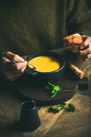Man in dark green winter sweater eating sweet corn and shrimp chowder soup from black bowl with toasted bread. Autumn or winter warming food