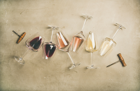 Flat-lay of red, rose and white wine in glasses and corkscrews over grey concrete background, top view, horizontal composition. Wine bar, winery, wine degustation concept 스톡 콘텐츠