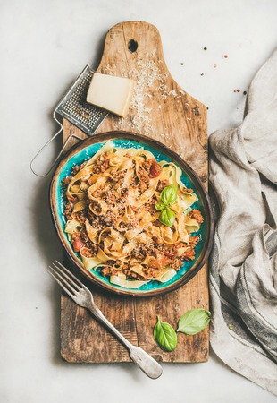 Italian traditional pasta dinner. Flat-lay of tagliatelle bolognese with minced meat, tomato sauce and parmesan cheese over rustic wooden board on white marble table, top view Фото со стока