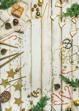 Getting ready for Christmas or New Year party. Flat-lay of holiday decoration toys, candles, rope, garlands, tree branches, sweater, candy cane over white background, top view, copy space